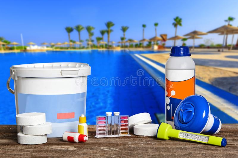 Equipment with chemical cleaning products and tools for the maintenance of the swimming pool. Newfangled equipment with chemical cleaning products and tools for stock image