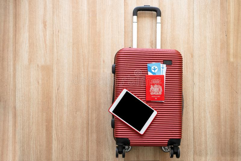 Equipment for company employees preparing to travel or work abroad,tablet and passport Placed on a red suitcase summertime concept stock photography