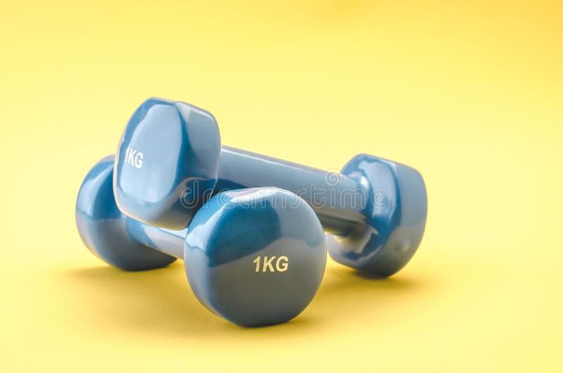 Equipment for fitness class/blue dumbbells on a yellow background stock image
