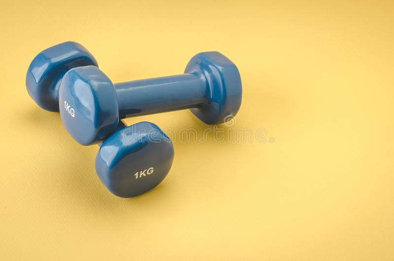 Equipment for fitness class/blue dumbbells on a yellow background. Copy space royalty free stock photography