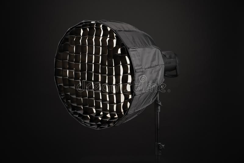 Equipment flash with honeycombs with octagonal softbox on the rack in studio close-up. On black background stock images