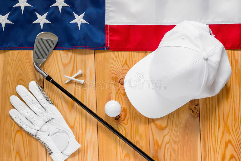 Equipment for golf and an American flag on a wooden floor. View from above stock image