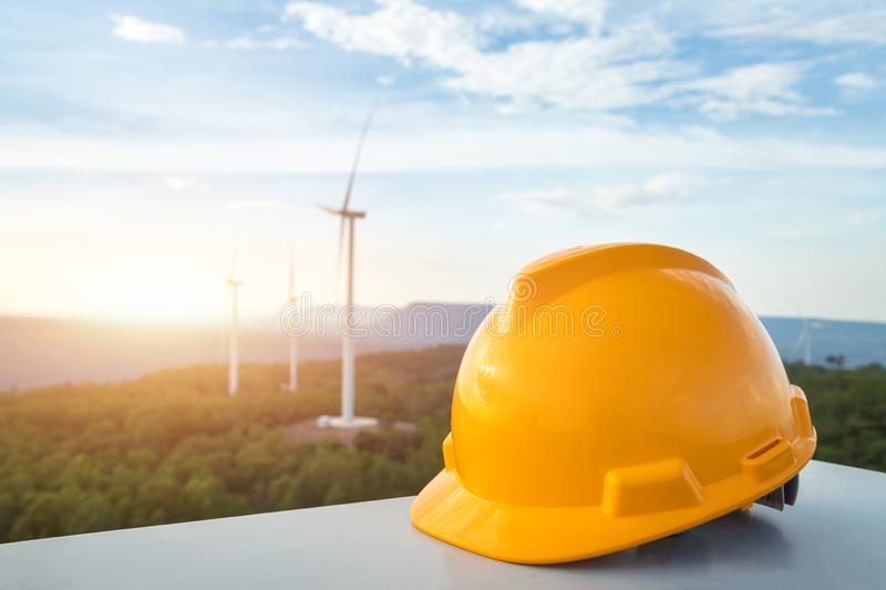 Equipment helmet in construction site and engineer inspection and progress check wind turbine at construction site background royalty free stock photography