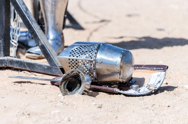 Equipment knight - the participant in the knight festival - shield, sword, helmet and glove lie on the ground near the lists royalty free stock images