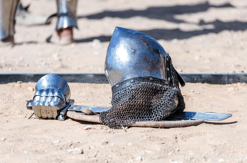Equipment knight - the participant in the knight festival - shield, sword, helmet and glove lie on the ground near the lists stock photo