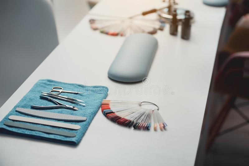 Equipment and manicure utensils situating on desk. Different appliance for creating manicure and nail polish colours on palette situating on table in beauty stock images