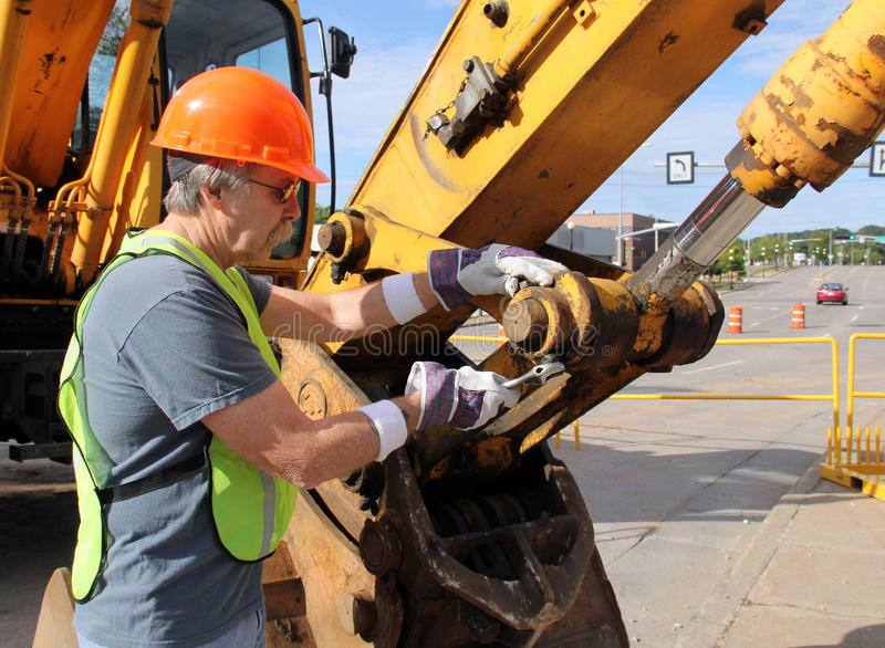 Equipment Mechanic. Heavy equipment mechanic working with a wrench on a nut stock photography
