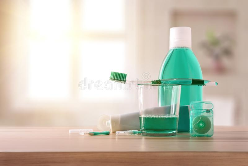 Equipment for oral hygiene on wood table in bathroom general. Equipment for oral hygiene on wood table in bathroom with window in the background. Horizontal stock photos