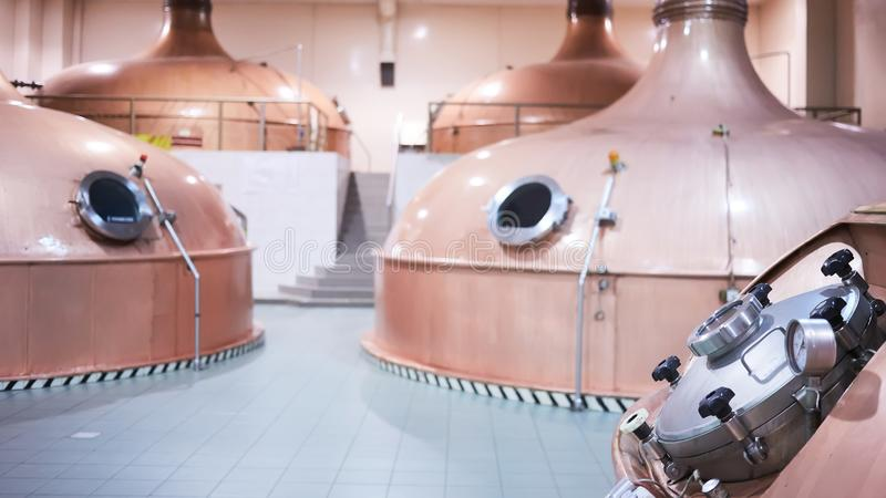 Equipment for preparation of beer. Lines of cooper tanks in brewery. Manufacturable process of brewage. Mode of beer. Production. Inside view of modern stock photography