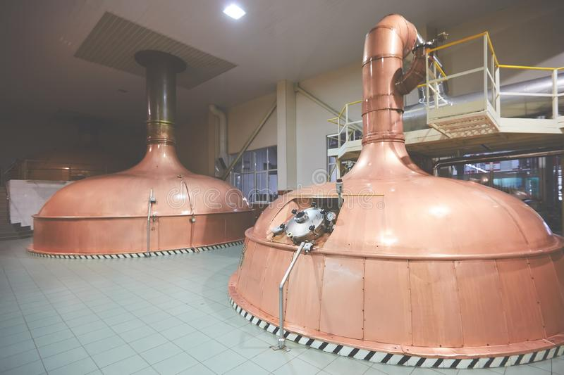 Equipment for preparation of beer. Lines of cooper tanks in brewery. Manufacturable process of brewage. Mode of beer. Production. Inside view of modern stock photo
