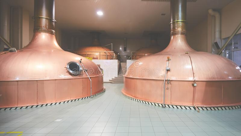 Equipment for preparation of beer. Lines of cooper tanks in brewery. Manufacturable process of brewage. Mode of beer. Production. Inside view of modern royalty free stock image