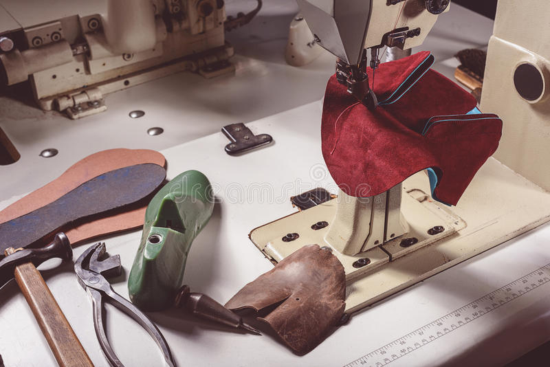 Equipment for shoe making on a table. Piece of new shoes on a sewing machine with some tools, close up royalty free stock photography