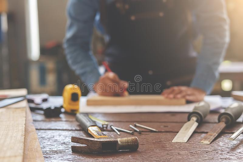 Equipment on wooden desk with man working in workshop background.  royalty free stock photography