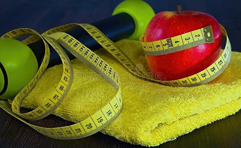 Fitness theme: red apple with measuring tape on a yellow towel. royalty free stock images