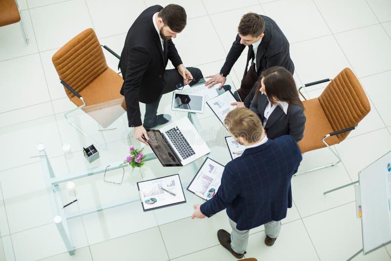 equipo acertado del negocio que discute comercializando gráficos antes de la reunión imagenes de archivo