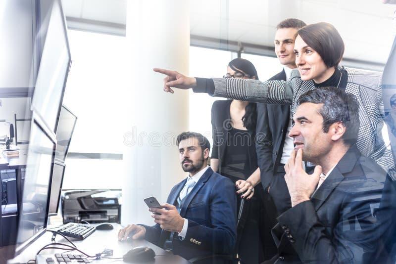 Equipo acertado del negocio que mira los datos comerciales sobre las pantallas de ordenador en oficina corporativa fotos de archivo libres de regalías