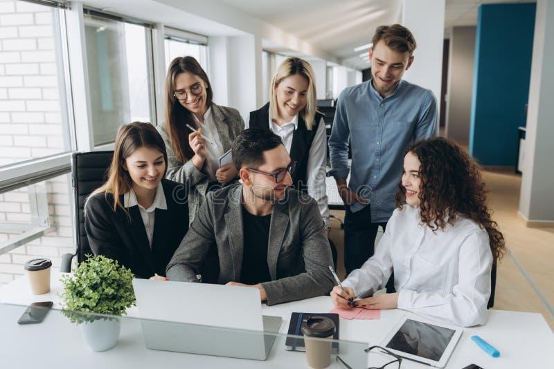 Equipo acertado Grupo de hombres de negocios jovenes que trabajan y que comunican junto en oficina creativa imagenes de archivo