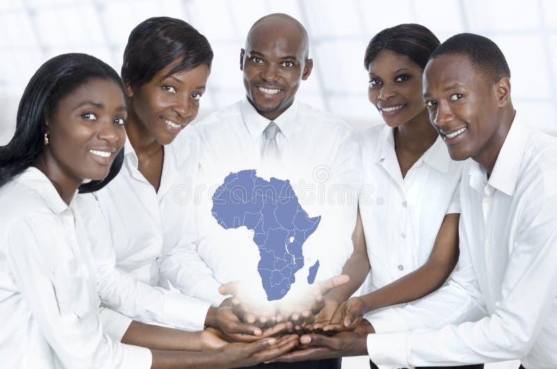 Equipo africano del negocio con el mapa de África fotografía de archivo