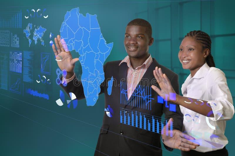 Equipo africano del negocio que trabaja en pantalla táctil virtual imagen de archivo