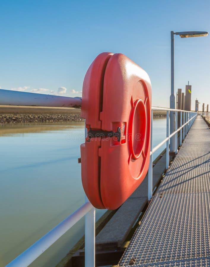Equipo anaranjado de la boya de vida en un embarcadero de acero largo foto de archivo libre de regalías