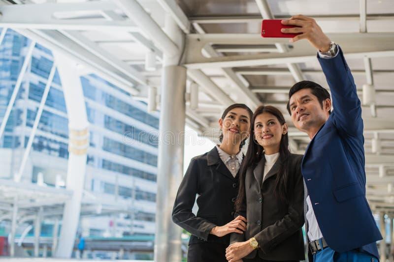 Equipo asiático del negocio que toma un selfie con smartphone en la ciudad imagenes de archivo