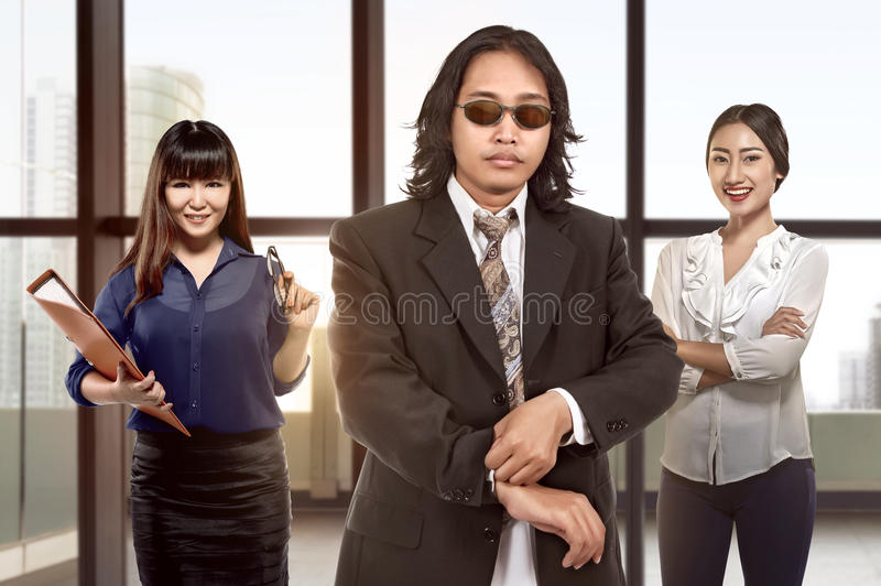 Equipo asiático joven de la mujer de negocios que se coloca detrás del jefe imágenes de archivo libres de regalías