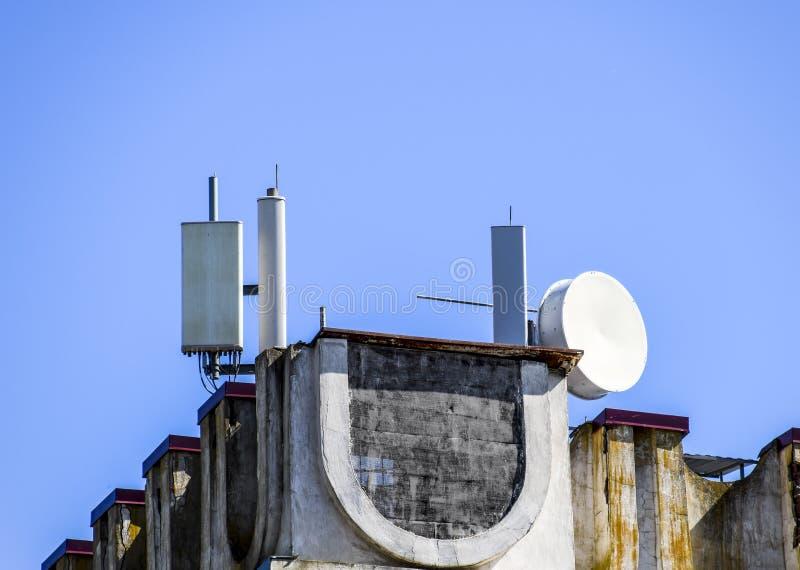 Equipo celular en el tejado del edificio Reflectores sobre los repetidores de la señal imagenes de archivo