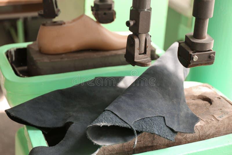 Equipo con el cuero para los zapatos de costura en taller fotografía de archivo