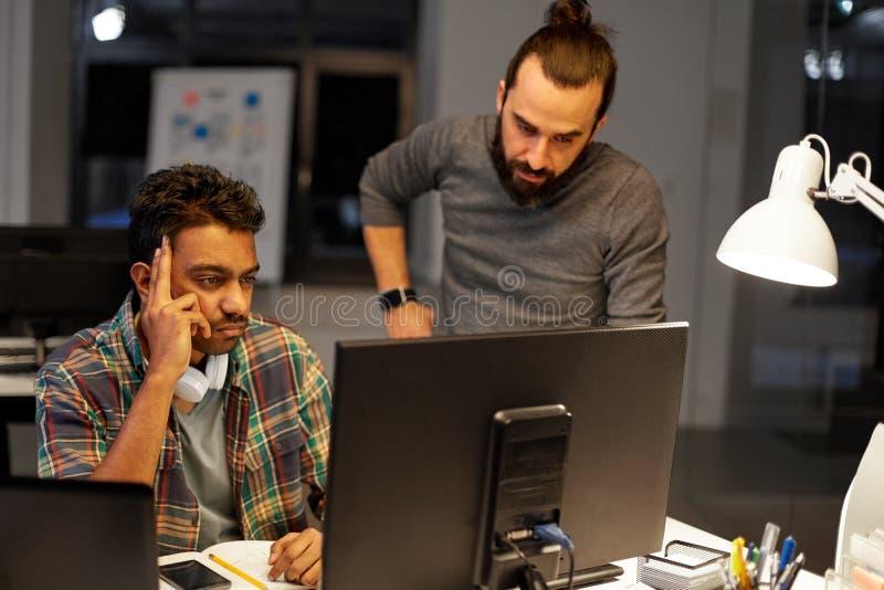 Equipo creativo con el ordenador que trabaja tarde en la oficina imagen de archivo