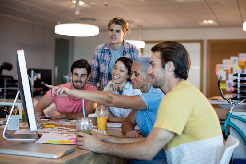 Equipo creativo del negocio que discute mientras que trabaja junto en PC de sobremesa foto de archivo libre de regalías