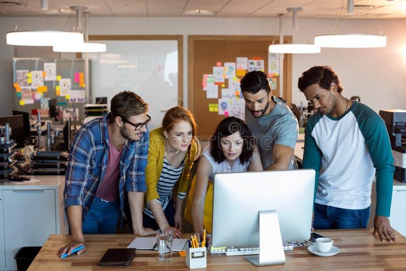Equipo creativo del negocio que trabaja junto en PC de sobremesa foto de archivo