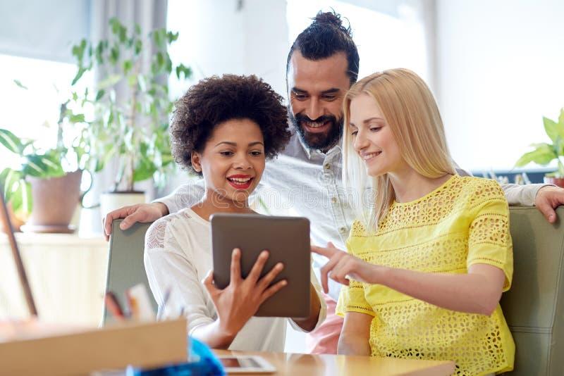 Equipo creativo feliz con PC de la tableta en oficina imagen de archivo libre de regalías