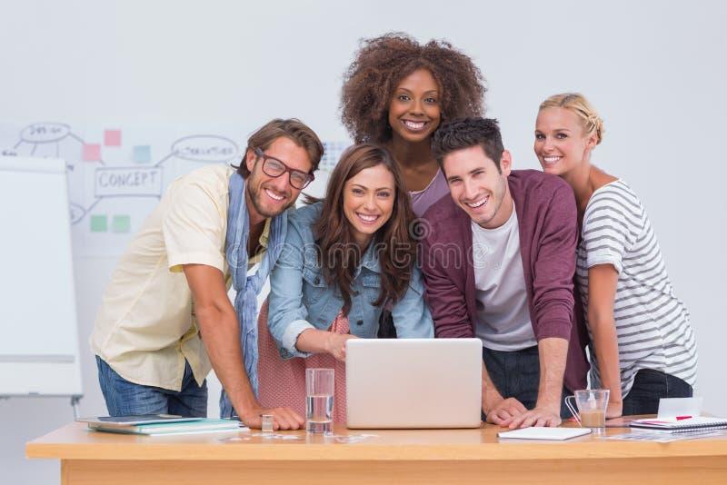 Equipo creativo que se coloca en el escritorio con el ordenador portátil foto de archivo libre de regalías