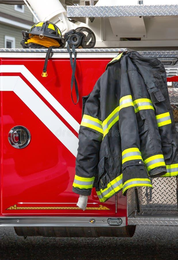 Equipo de asistencia al bombero que se encuentra en un camión de bomberos en el lugar del incendio fotografía de archivo libre de regalías