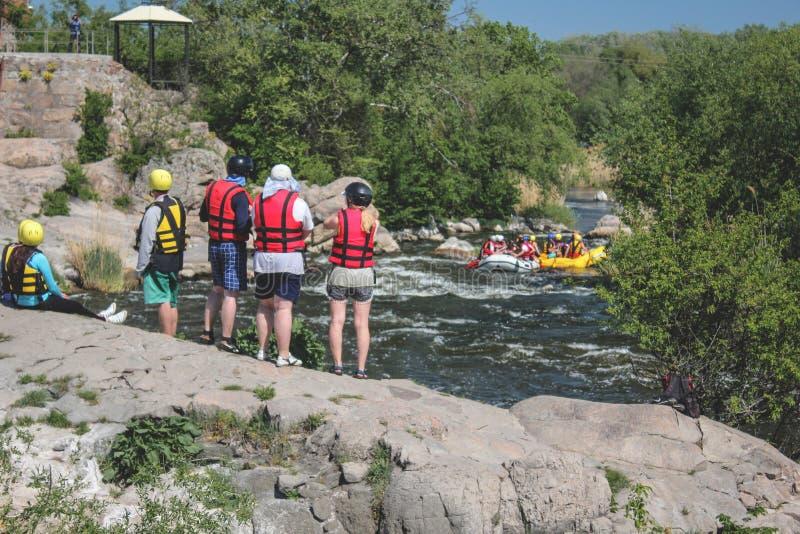 Equipo de atletas en chalecos salvavidas que miran la balsa en el río fotos de archivo libres de regalías