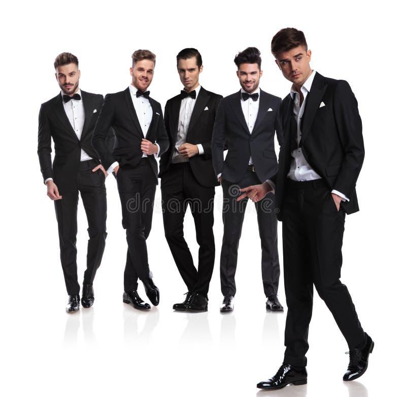 Equipo de cinco novios con los fingeres de rotura y caminar del líder foto de archivo