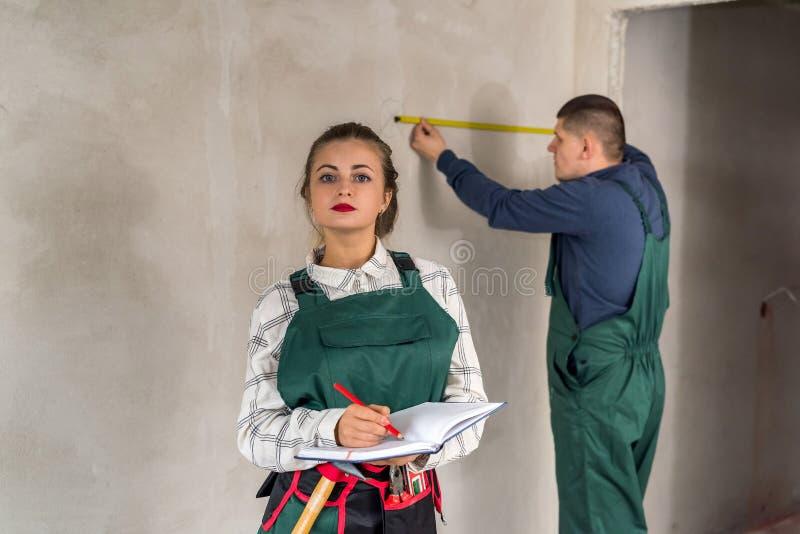 Equipo de constructores que miden las paredes y que escriben en libreta imagenes de archivo