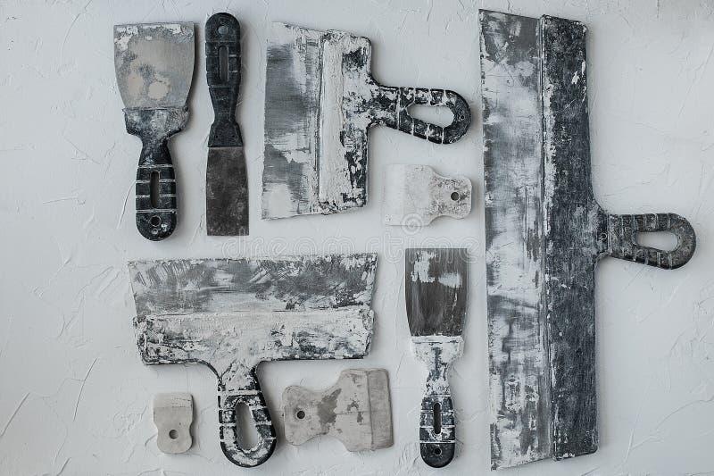 Equipo de cuchillos de masilla Espátulas con el mortero restante Gastarbeiter o concepto del trabajador inmigrante foto de archivo libre de regalías