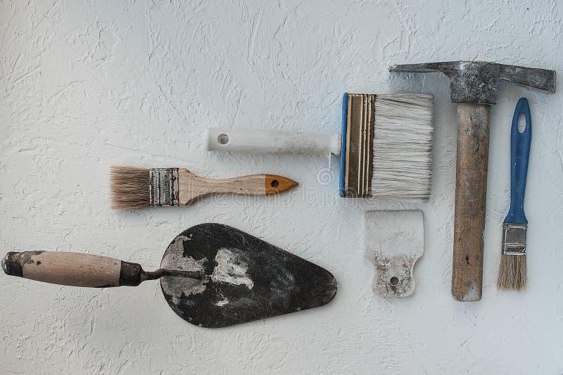 Equipo de cuchillos de masilla Espátulas con el mortero restante Gastarbeiter o concepto del trabajador inmigrante imágenes de archivo libres de regalías