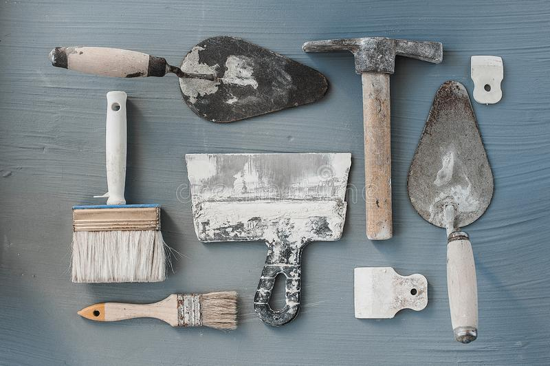 Equipo de cuchillos de masilla Espátulas con el mortero restante Gastarbeiter o concepto del trabajador inmigrante imagen de archivo
