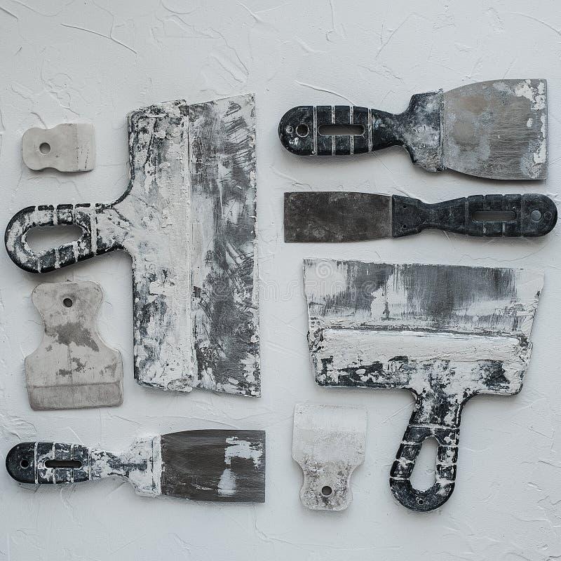 Equipo de cuchillos de masilla Espátulas con el mortero restante Gastarbeiter o concepto del trabajador inmigrante fotos de archivo libres de regalías