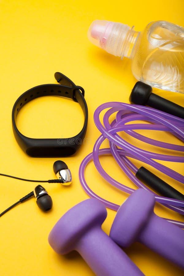 Equipo de deporte Pesas de gimnasia, cuerda que salta, pulsera de la aptitud, agua y auriculares en un fondo amarillo foto de archivo