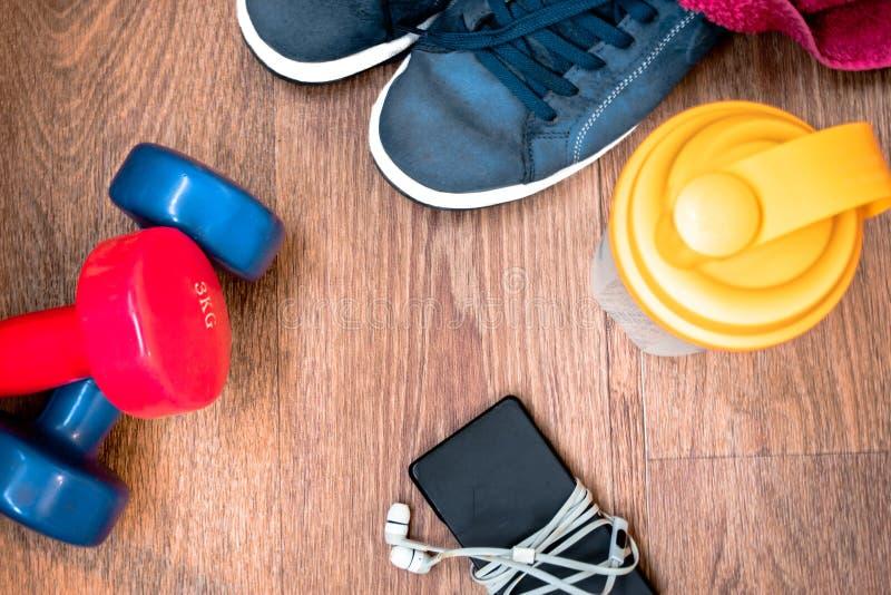Equipo de deportes en el piso de madera con las zapatillas de deporte, teléfono imagen de archivo libre de regalías