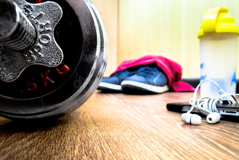 Equipo de deportes en el piso de madera con las zapatillas de deporte, teléfono imagenes de archivo