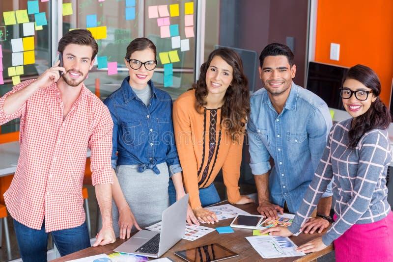 Equipo de diseñadores gráficos felices que se colocan en la tabla foto de archivo