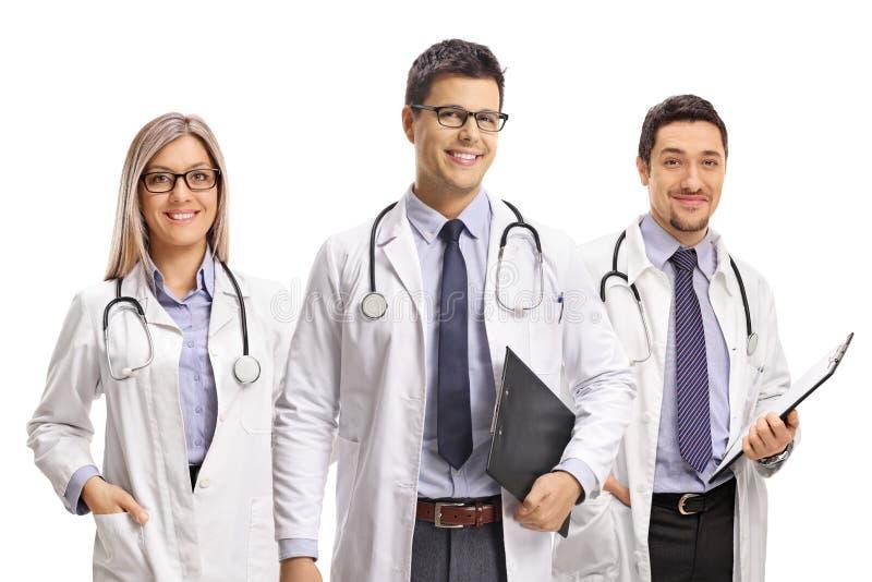 Equipo de doctores jovenes que presentan y que sonríen en la cámara foto de archivo