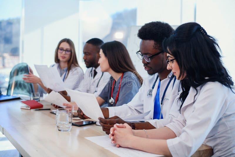 Equipo de doctores profesionales que tienen una reunión en la sala de conferencias en el hospital moderno Atenci?n sanitaria y m? foto de archivo libre de regalías