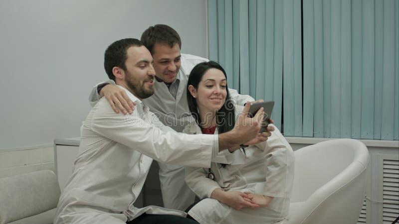 Equipo de doctores que toman el selfie todo junto en una oficina médica fotografía de archivo