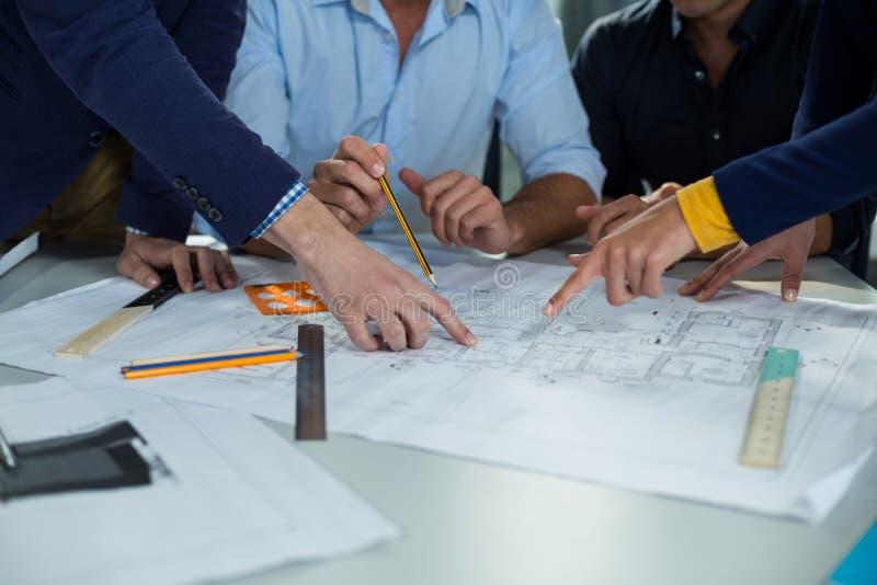 Equipo de ejecutivos de operaciones que discuten el modelo en la reunión imagen de archivo libre de regalías