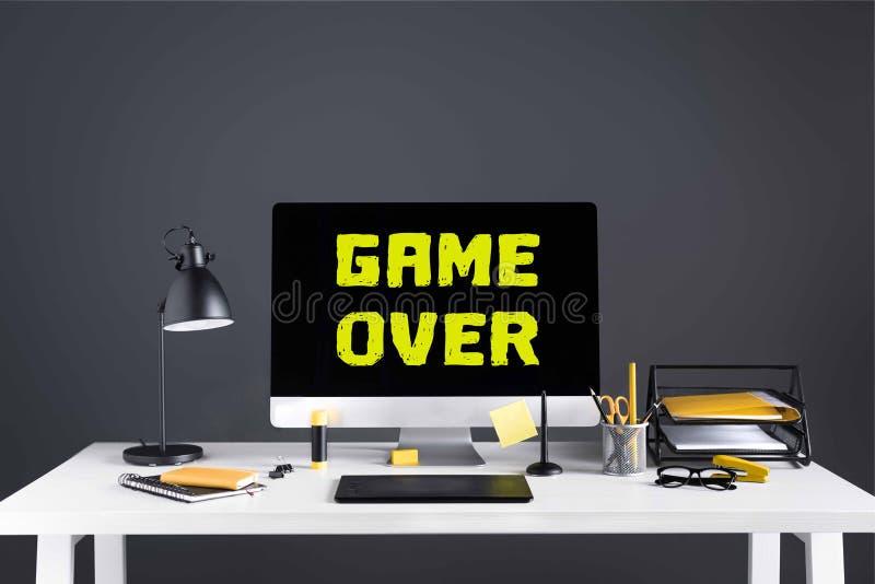 Equipo de escritorio con el juego sobre la inscripción en la pantalla, la tableta de gráficos y materiales de oficina imagen de archivo